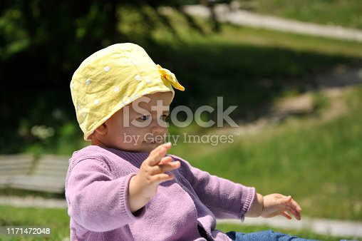 540510130istockphoto Adorable little girl with yellow hat sitting on the grass in the summer. 1171472048