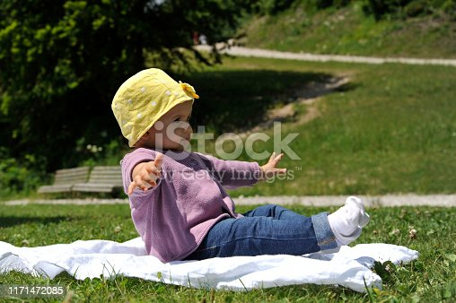 540510130istockphoto Adorable little girl with yellow hat sitting on the grass in the summer. 1171472085