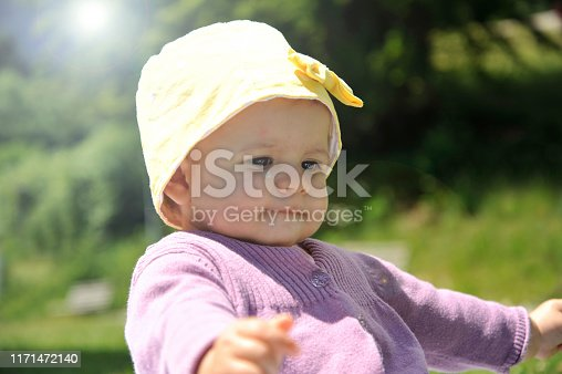 540510130istockphoto Adorable little girl with yellow hat sitting on the grass in the summer. 1171472140