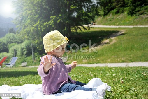 540510130istockphoto Adorable little girl with yellow hat sitting on the grass in the summer. 1171538586