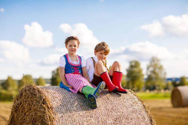 entzückende kleine kind jungen und mädchen in bayerischen trachten im weizenfeld auf heuhaufen - sommerfest kindergarten stock-fotos und bilder