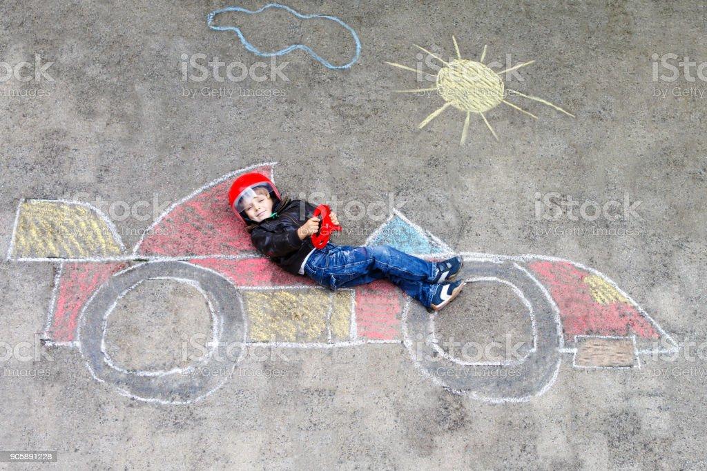Entzückende junge Kind zeichnen mit bunten Kreide Rennen Auto Bild auf Asphalt. – Foto