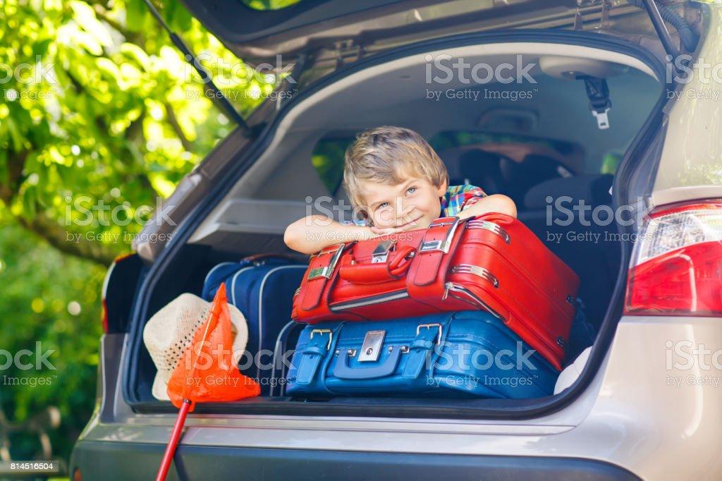 Entzückende kleine Kind junge sitzen im Kofferraum eines Autos kurz vor der Abreise für Sommerurlaub mit seinen Eltern. – Foto