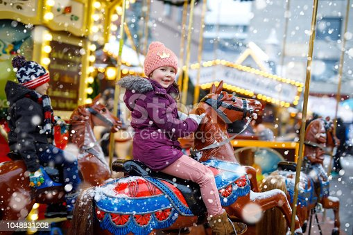 Adorable little kid girl riding on a merry go round carousel horse at Christmas funfair or market, outdoors. Happy child having fun on traditional family xmas market in Munich, Germany.