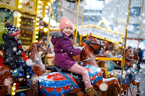 Adorable little kid girl riding on a carousel horse at Christmas funfair or market, outdoors.