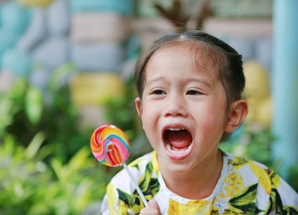 Adorable little laughing girl holding big colorful lollipop picture id867657672?b=1&k=6&m=867657672&s=612x612&w=0&h=ir8zvpo uuoq6aokls2ecqnljpqeg4ybqda28xmjsyk=