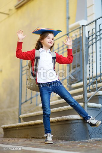 istock Adorable little schoolgirl studying outdoors on bright autumn day. Young student doing her homework. Education for small kids. 1027400706