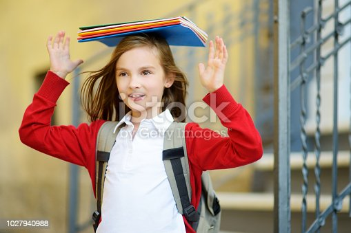 istock Adorable little schoolgirl studying outdoors on bright autumn day. Young student doing her homework. Education for small kids. 1027940988