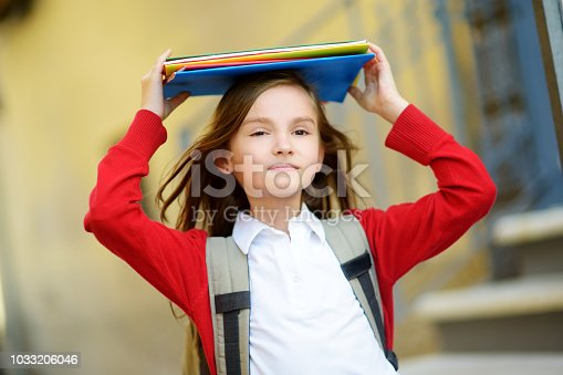 istock Adorable little schoolgirl studying outdoors on bright autumn day. Young student doing her homework. Education for small kids. 1033206046