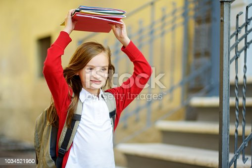 istock Adorable little schoolgirl studying outdoors on bright autumn day. Young student doing her homework. Education for small kids. 1034521950