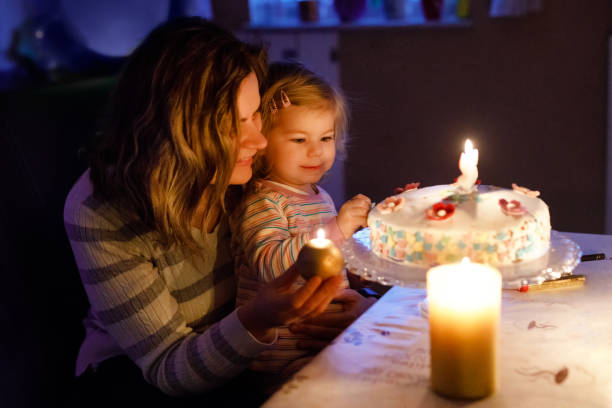 Adorable little toddler girl celebrating second birthday. Baby child daughter and young mother blowing candles on cake and candles. Happy healthy family portrait, mom love and happiness Adorable little toddler girl celebrating second birthday. Baby child daughter and young mother blowing candles on cake and candles. Happy healthy family portrait, mom love and happiness. birthday wishes for daughter stock pictures, royalty-free photos & images