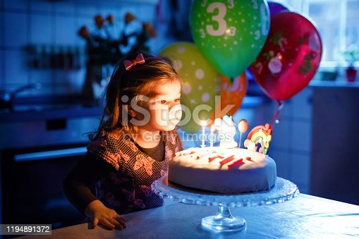 819811074 istock photo Adorable little toddler girl celebrating third birthday. Baby toddler child with homemade unicorn cake, indoor. Happy healthy toddler is suprised about firework sparkler and blowing candles on cake 1194891372