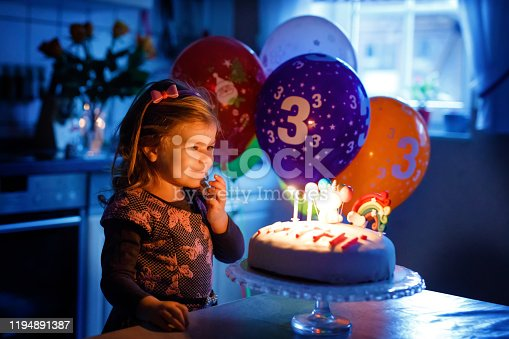 819811074 istock photo Adorable little toddler girl celebrating third birthday. Baby toddler child with homemade unicorn cake, indoor. Happy healthy toddler is suprised about firework sparkler and blowing candles on cake 1194891387