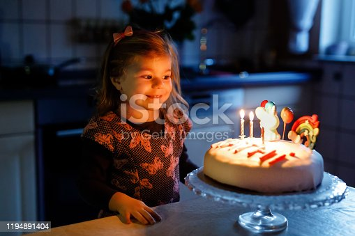 819811074 istock photo Adorable little toddler girl celebrating third birthday. Baby toddler child with homemade unicorn cake, indoor. Happy healthy toddler is suprised about firework sparkler and blowing candles on cake 1194891404