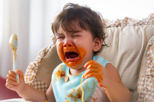 Adorable little toddler girl or infant baby crying when unsatisfied when finished eating food on baby chair. Cute infant girl get hungry and want more food. Mix race daughter get dirty Kid get tantrum stock photo