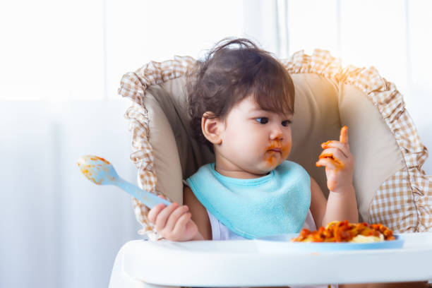 Adorable little toddler girl or infant baby eating delicious spaghetti food with tomato sauce on baby chair. Cute infant girl practice eating food by using spoon. Mix race daughter look dirty hand stock photo