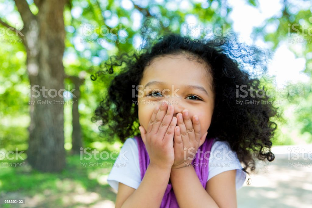 Adorable mixed race girl in the park stock photo