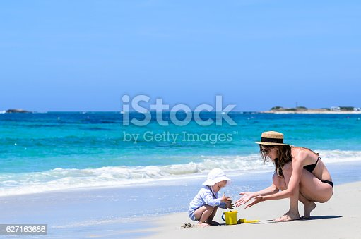 istock Adorable mother and little daughter building sandcastles at beach 627163686