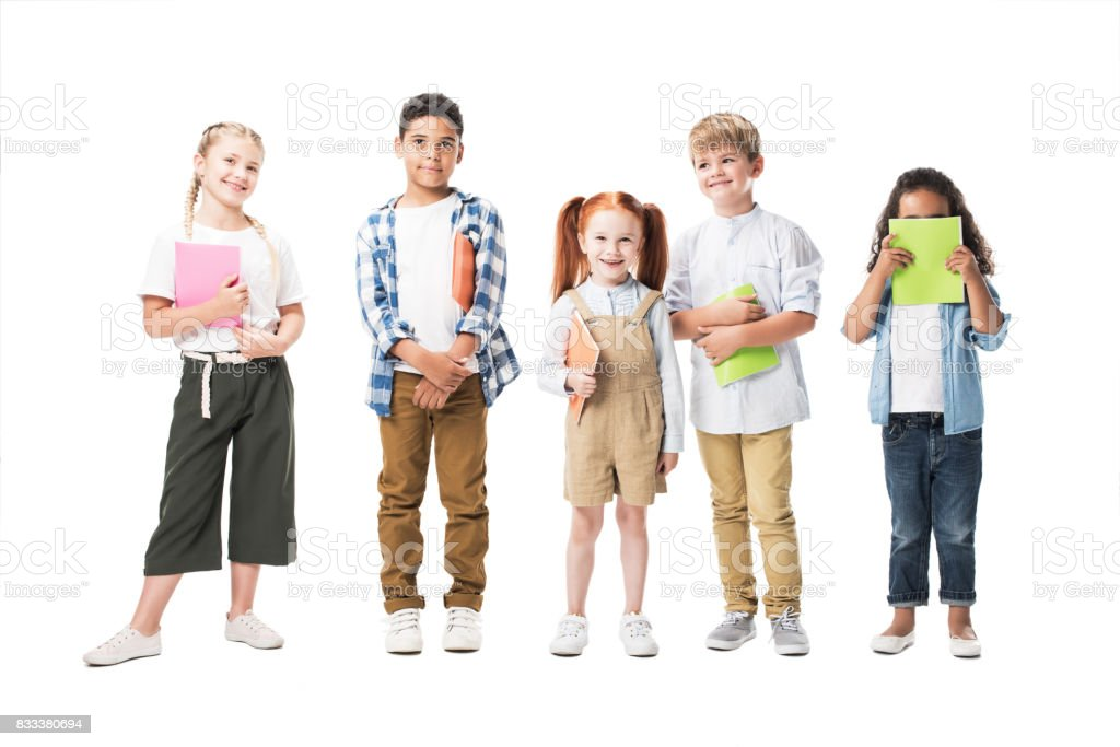 adorable multiethnic children holding textbooks and smiling at camera isolated on white stock photo