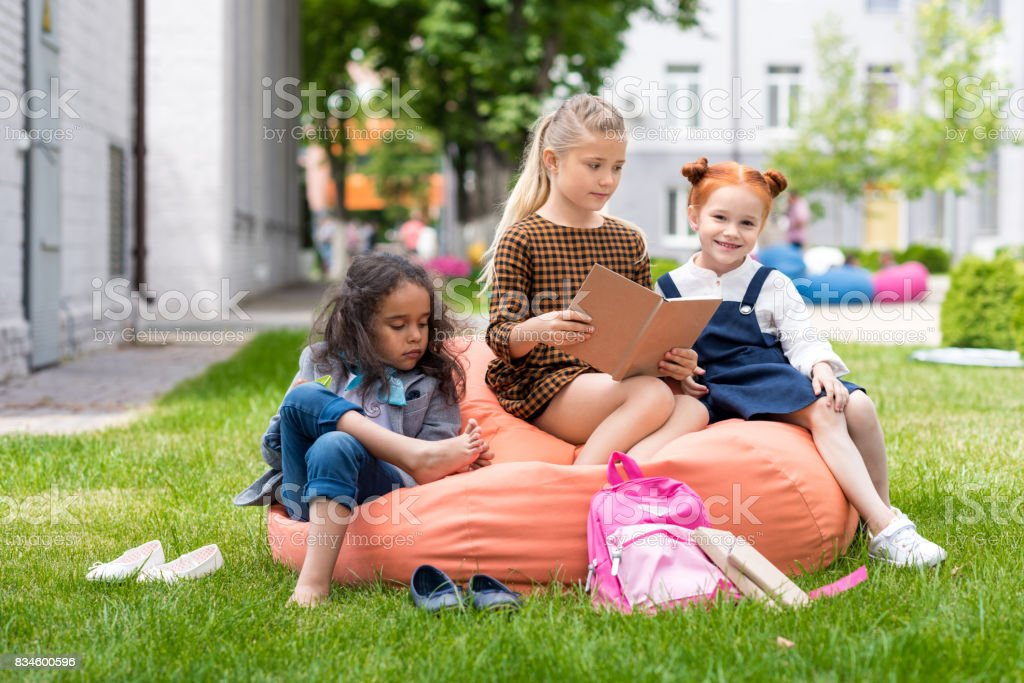 adorable multiethnic schoolgirls sitting on bean bag chair and reading book on schoolyard stock photo