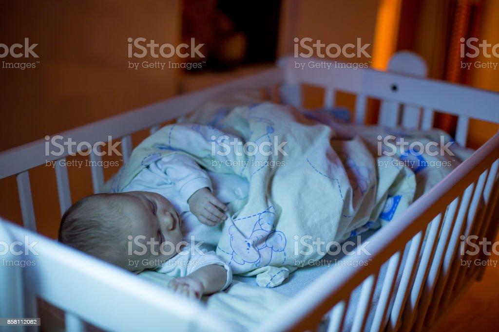 Adorable niño de recién nacido durmiendo en la cuna por la noche foto de stock libre de derechos