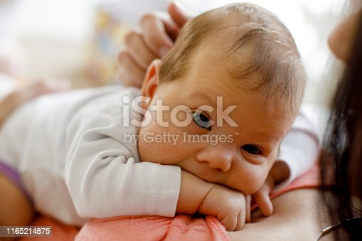 Close up shot of cute newborn baby girl being held and cuddled by her mother while resting on her chest and looking away.