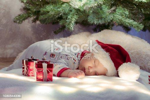 istock Adorable newborn baby sleeping under Christmas tree near gifts on lighting blanket. 1030544336