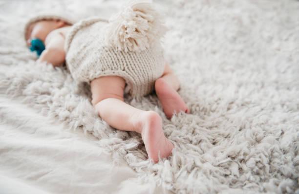 entzückendes neugeborenes schläft in niedlichen strickoutfit auf flauschiger decke - jungendecken häkeln stock-fotos und bilder