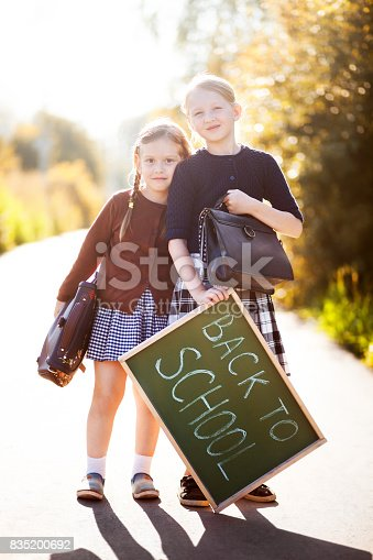 Adorable old-fashioned little 6 years old and 10 years old girls smiling, holding school bags and back to school chalkboard. Preschooler and schoolgirl sisters, schoolkids are happy back to school. Copyspace, empty space for text.