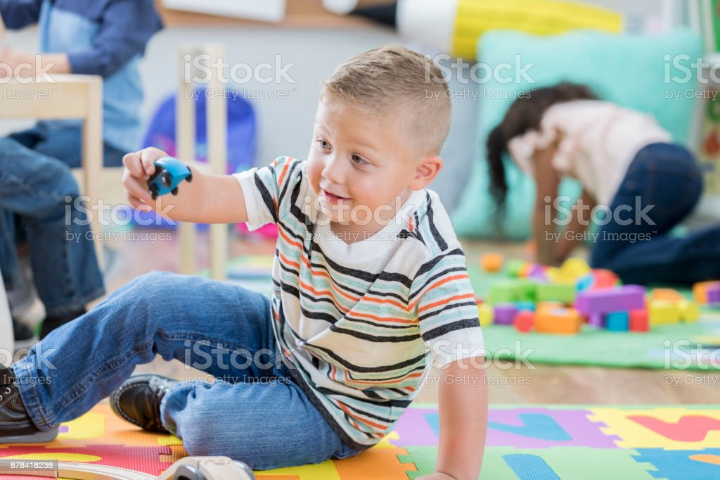 Cute Caucasian male preschool student enjoys playing with a wooden...