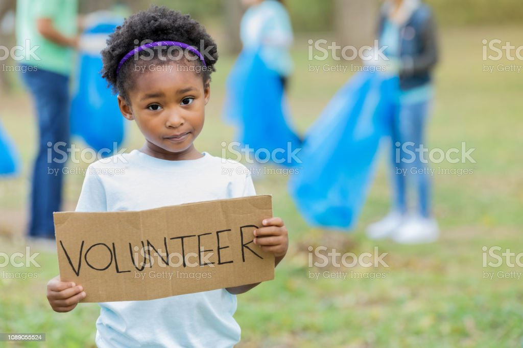 Young girl holds a \'volunteer\' sign while helping her family during a...