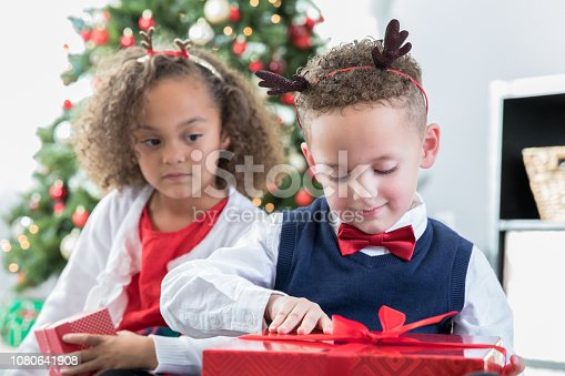 istock Adorable preschool age siblings opening Christmas gifts together 1080641908