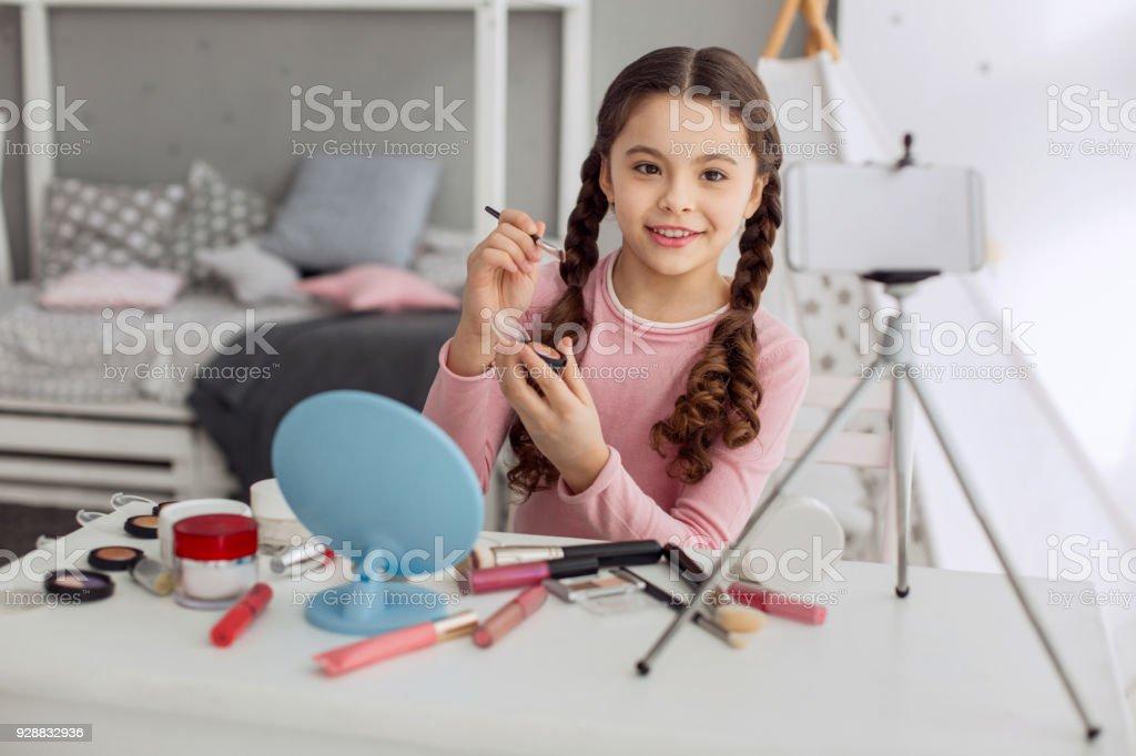Adorable pre-teen girl filming eye shadows review stock photo