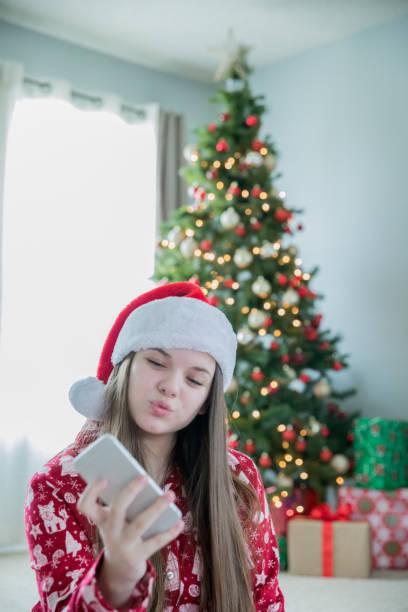 entzückende vorunterten mädchen, die selfie mit neuem smartphone am weihnachtsmorgen - weihnachtsprogramm stock-fotos und bilder