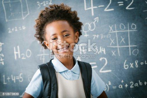 istock Adorable private school kindergarten girl smiling in front of blackboard 510973839
