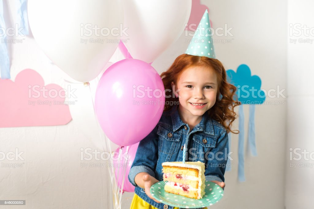 adorable redhead girl on party hat holding birthday cake and smiling at camera stock photo