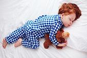 フランネル パジャマのぬいぐるみと寝ている愛らしい赤毛幼児赤ちゃん