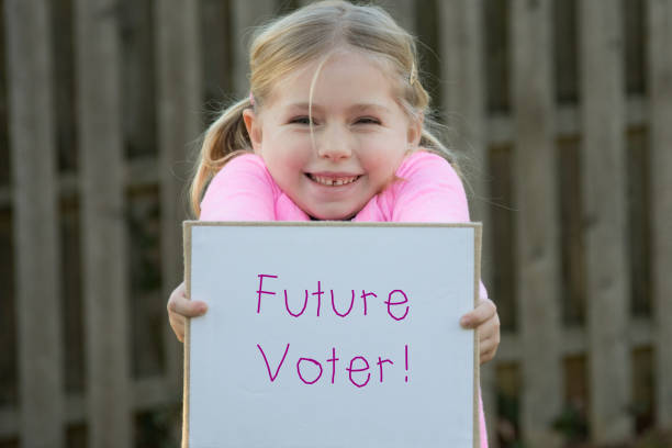 adorable school age girl holding future voter sign - vote sign stock photos and pictures