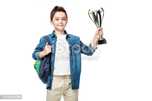 1016623732istockphoto adorable schoolboy with backpack holding winner cup isolated on white 1016623266