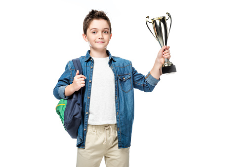 1016623732 istock photo adorable schoolboy with backpack holding winner cup isolated on white 1016623266