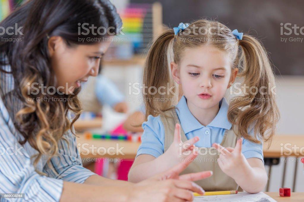 Adorable schoolgirl counts on fingers in class stock photo