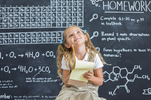 Intelligent young schoolgirl thinks about something while in front of the chalkboard in a science classroom.
