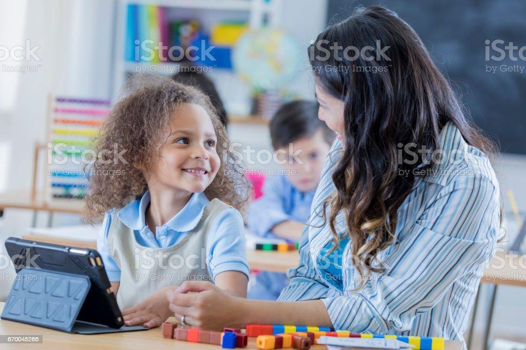 Adorável menina usa tablet digital na escola - foto de acervo
