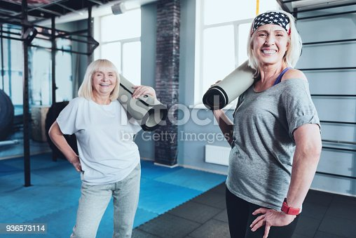 936573360 istock photo Adorable senior female friends posing with mats 936573114