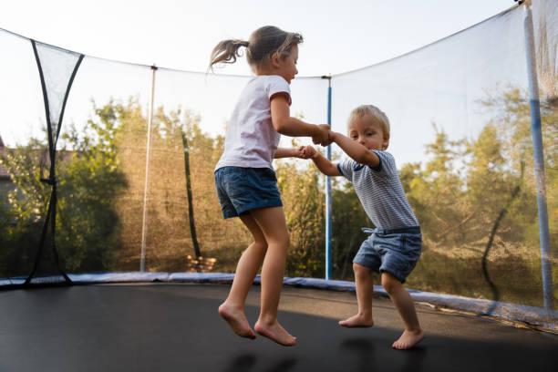 Entzückende Geschwister zusammen auf Trampolin Springen – Foto