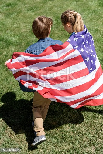 istock adorable siblings holding american flag and running outdoors, celebrating 4th july - Independence Day 802425354