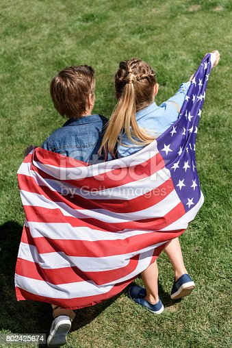 istock adorable siblings with american flag having fun outdoors, America's Independence Day concept 802425674
