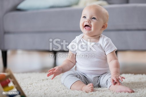 istock Adorable smiling baby sitting on floor and looking up 865900660