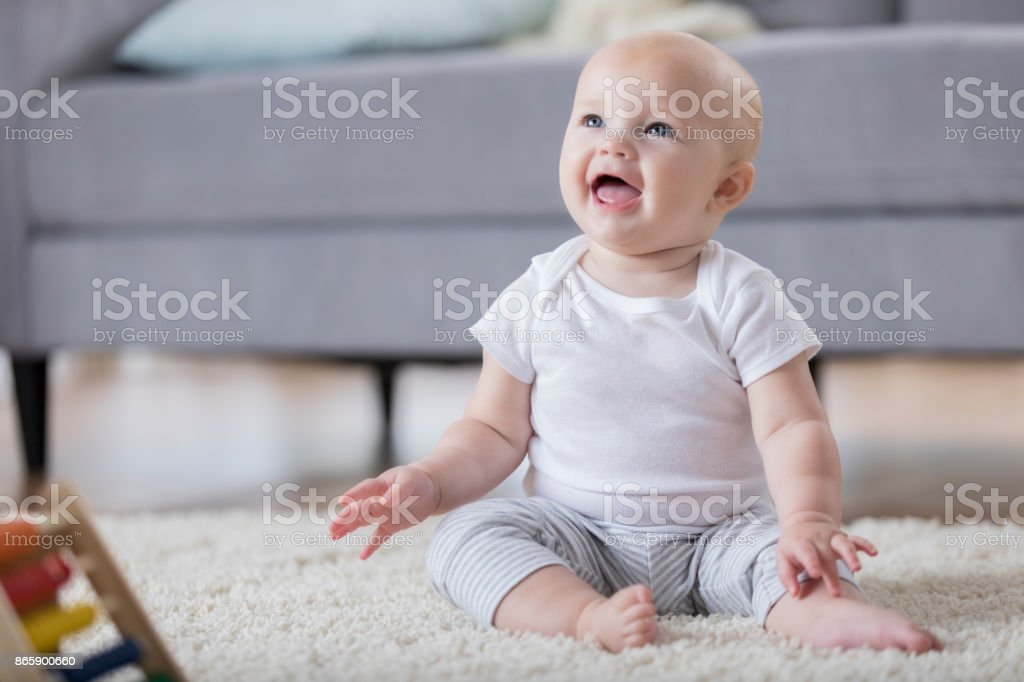 Adorable smiling baby sitting on floor and looking up stock photo