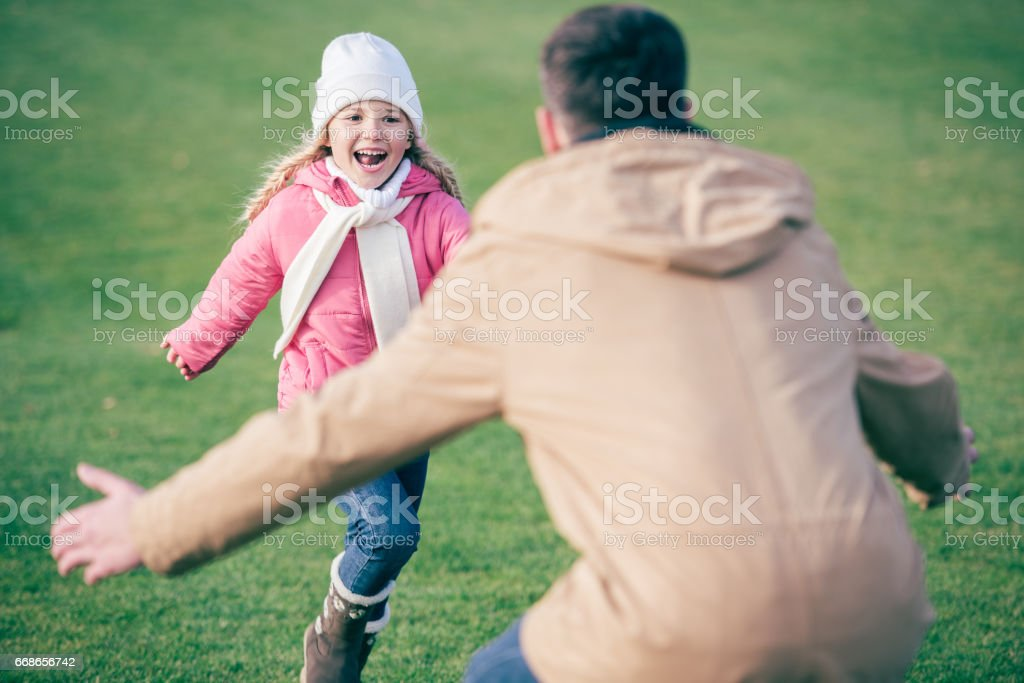 Adorable smiling girl running to father stock photo